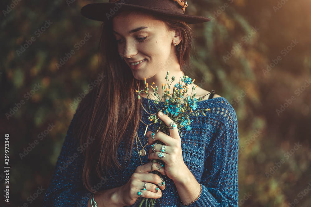 Fototapeta Happy attractive autumn brunette boho chic woman in a brown hat and knitted blue sweater with bouquet of wildflowers in hands in autumn forest outdoors in fall. Boho fashion