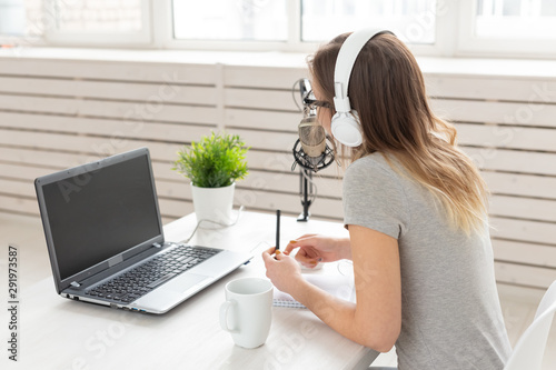 Valokuva  Radio, DJ, blogging and people concept - Smiling woman sitting in front of micro