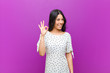 canvas print picture - young pretty latin woman feeling happy, relaxed and satisfied, showing approval with okay gesture, smiling against purple wall