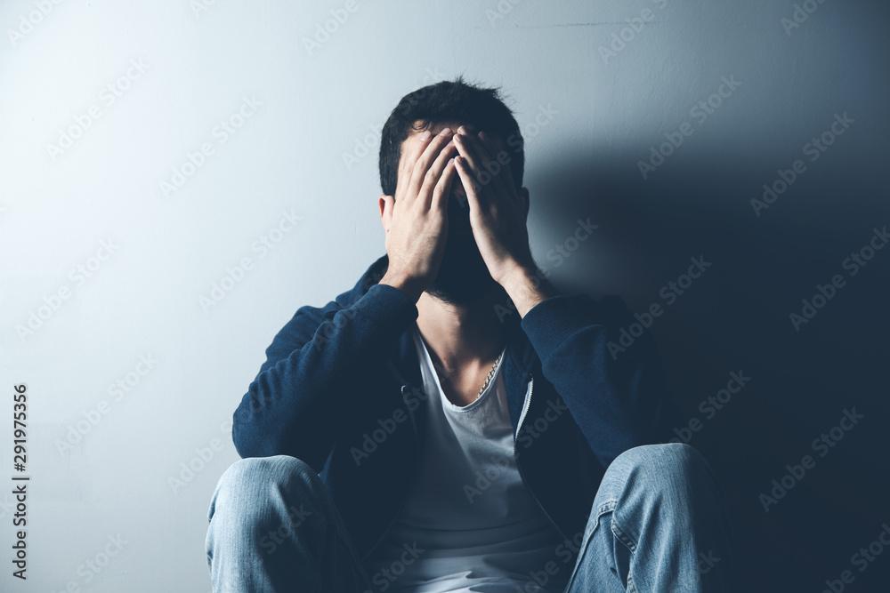 Fototapeta sad man sitting on ground on dark background