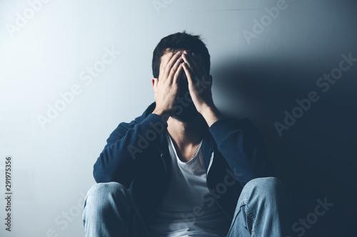 sad man sitting on ground on dark background Fototapeta