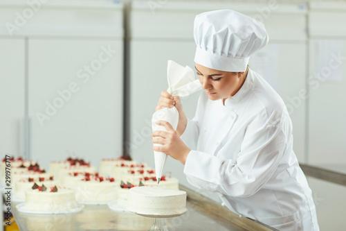 Fototapeta Confectioner decorating cake in pastry shop.