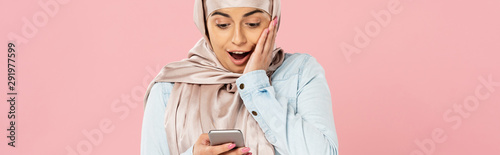 Fotomural  shocked muslim girl in hijab using smartphone isolated on pink