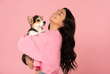 Happy Woman Holding Welsh Corgi Puppy, Isolated On Pink