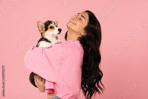 happy woman holding Welsh Corgi puppy, isolated on pink Fototapet