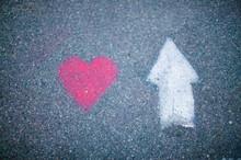 Drawing Love Symbol And Arrow On Asphalt.