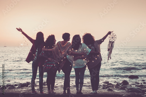 Love friendship and celebration time concept image with group of women friends viewed from back enjoying the beautiful coloured sunset in front of the ocean - feeling with nature and joyful for world