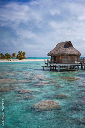 Fototapeta Vertical of overwater bungalow luxury resort in calm tropical lagoon paradise