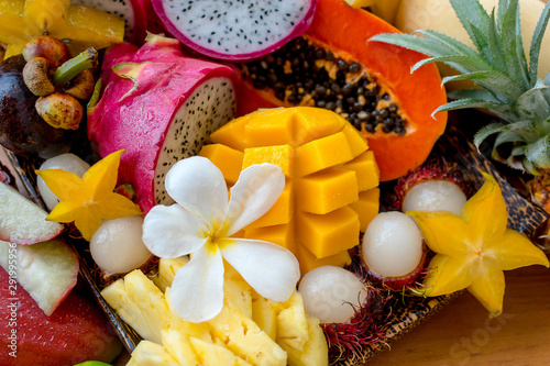 Juicy ripe tropical Thai fruits on a wooden dish. - 291995956