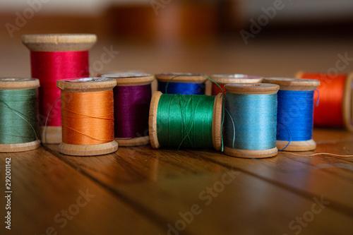 Colorful closeup of vintage wooden spools of thread Fototapeta