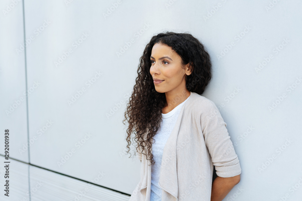 Fototapeta Young woman relaxing against a wall thinking