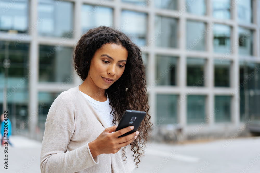 Fototapeta Young woman reading a message on her cellphone
