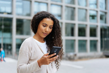 Young Woman Reading A Message On Her Cellphone