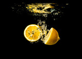 Fresh yellow lemon halves in water splash on black background with lots of air bubbles.