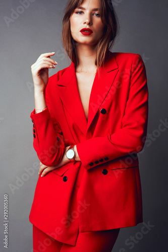 Young woman in red suit. Grey background Wall mural