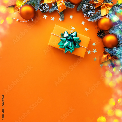 Christmas composition. Orange background with gift box and decorations. Copy space. Holiday concept.