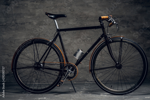 Türaufkleber Fahrrad Black retro bicycle is parked at photo studio on the dark background.