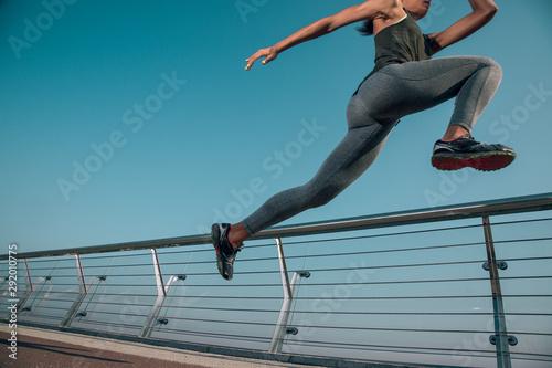 Αφίσα Sportswoman jumping up high in the air stock photo