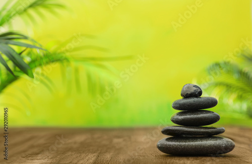 Obraz Table with stack of stones and blurred green leaves on background, space for text. Zen concept - fototapety do salonu