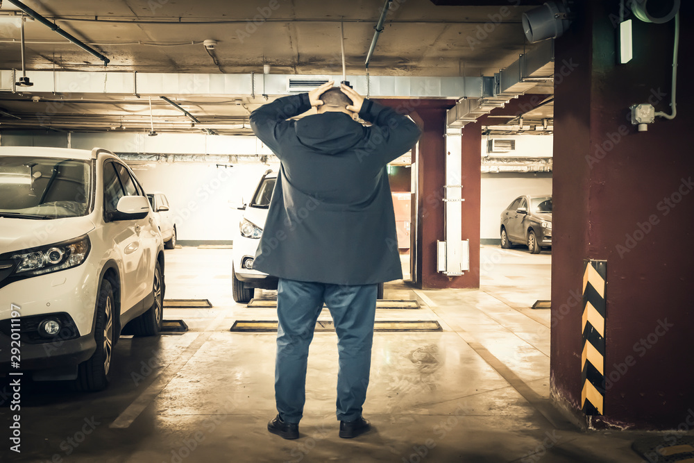 Fototapeta Astonished and surprised man discovered loss of car in underground garage parking lot. Stolen car concept, toned
