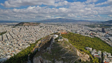 Aerial Drone Photo Of Iconic Mount Lycabettus Featuring Famous Church Of Saint George On Top With Beautiful Clouds And Deep Blue Sky, Athens Historic Centre, Attica, Greece