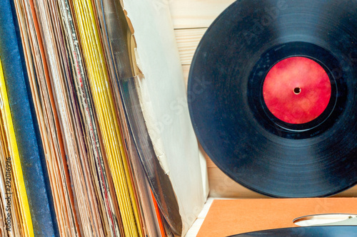 Vinyl record in front of a collection of albums, vintage process. Copy space for text - 292016996