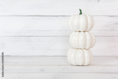 Stack of white pumpkin on white wood table with copy space.
