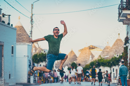 happy tourist take selfie photo jumping in Alberobello town, Apulia, southern Italy Wallpaper Mural
