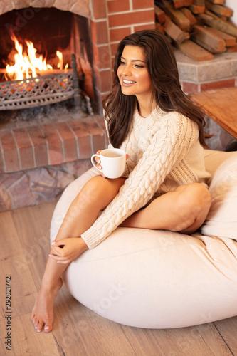 Girl relaxing near fireplace.