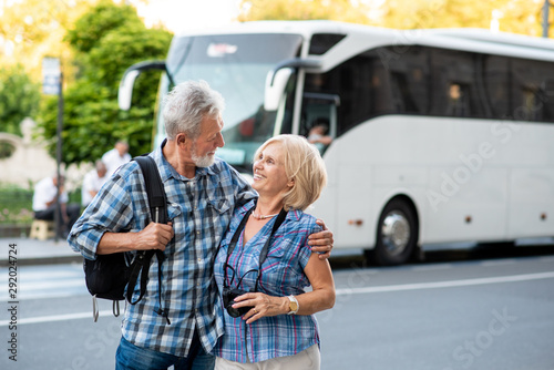 Stampa su Tela Happy senior couple of tourists hugging in front of tourist bus