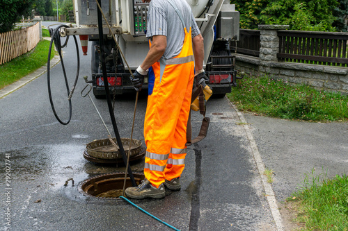 sewerage worker on street cleaning pipe #292027741