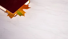 An Old Worn Book Of Burgundy With A Bookmark Of Yellow Autumn Maple Leaf Lies On  A White Marble Table, On Which There Is Plenty Of Room For Text