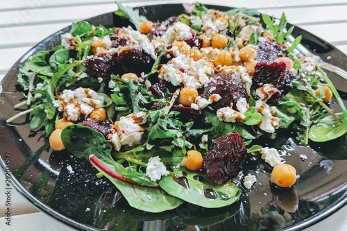 Closeup shot of a salad made out of vegetables, arugula, cheese, and chickpea, dipped in balsamic