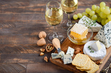 Cheese Plate With Grapes, Crackers, Honey, And Nuts On A Wooden Table.