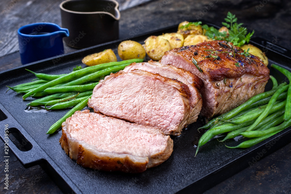 Fototapety, obrazy: Traditional roasted dry aged veal tenderloin with beans and potatoes offered as closeup on a modern design cast iron tray