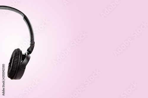 Black headphones on a pastel pink background. The concept of creating and listening to music. Comfortable headphones for listening to music. Creating sounds and listening to the foundations. - 292042580