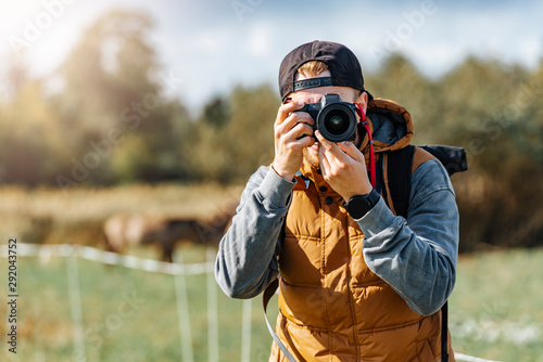 Photo Photographer in brown vest and black hat taking pictures with his camera during sunny summer day