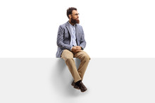 Bearded Man Sitting On A White Banner And Looking To The Side