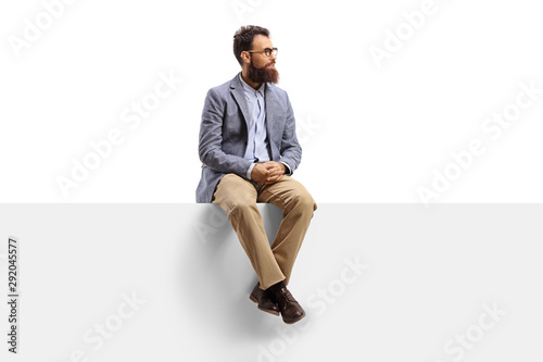 Fototapeta Bearded man sitting on a white banner and looking to the side obraz