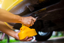 Hands Of Man Holding Yellow Car Towing Strap With Yellow Car. Yellow Car Towing. Towing Rope.