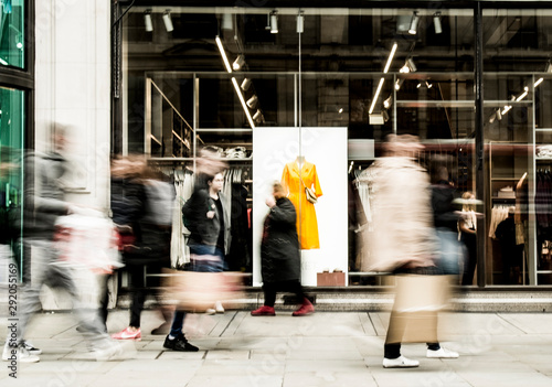 Fototapeta Motion blurred people walking past shop window obraz