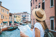 Hipster female backpacke standing on thel bridge in Venice and looking at the canal