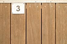 3, Number Three, Metal Plate On Wooden Teak Deck.