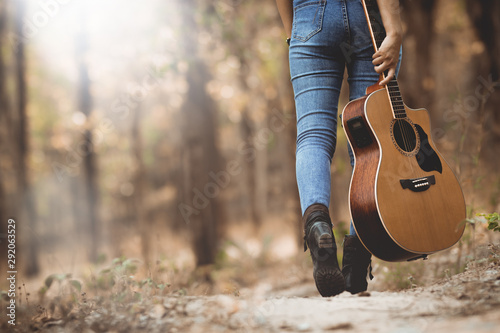 Asia woman  holding  the guitar walking into the forest with loneliness. - 292063529