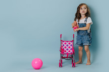 Little Girl Holding A Doll Next To A Pram And Pink Gymnastic Ball Over Blue