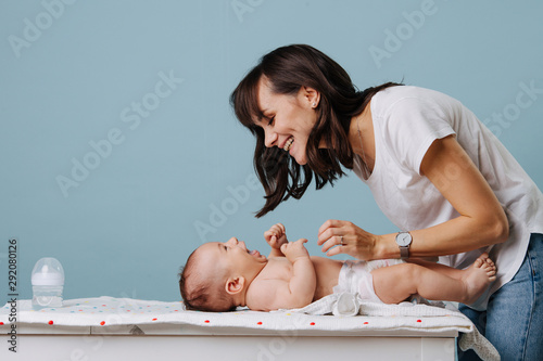 Photographie Mother changing diaper on her baby on table over blue background.