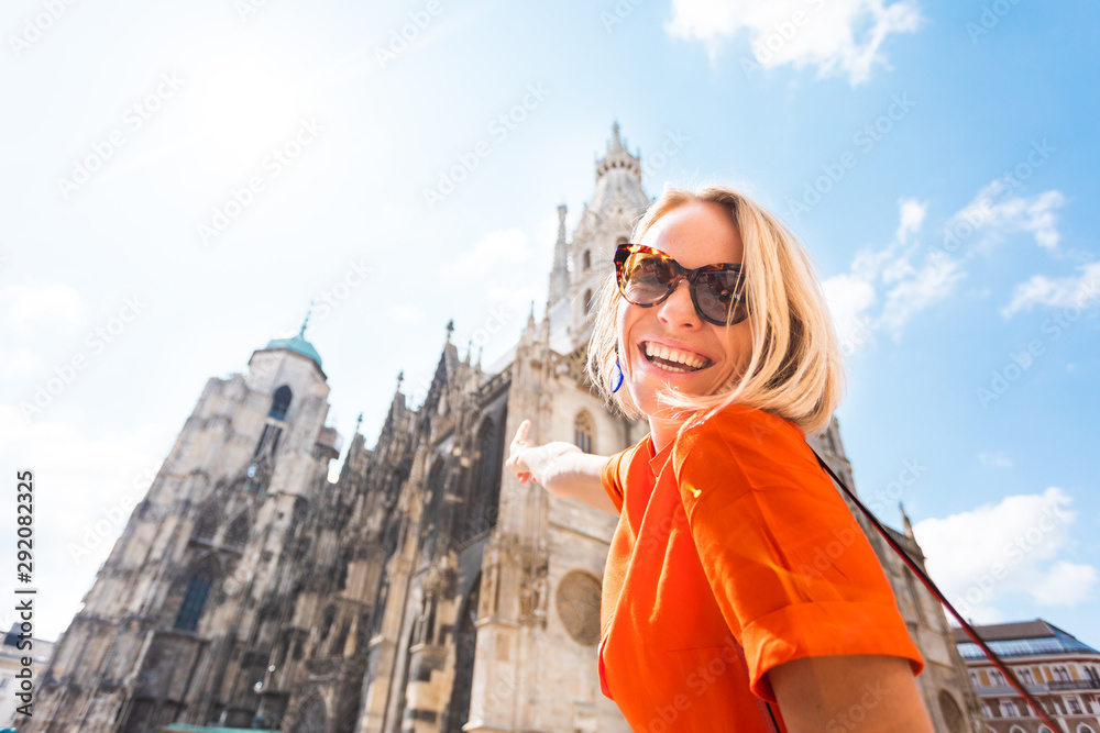 Fototapety, obrazy: A young woman in a bright orange dress stands on the background of St. Stephen's Cathedral in Vienna, Austria