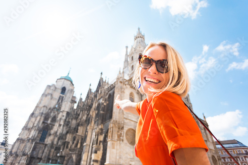 A young woman in a bright orange dress stands on the background of St Fotobehang