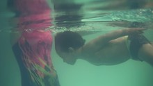 A Small Swimmer Diving Into Th...