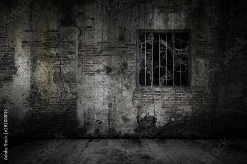 Spoed Fotobehang Baksteen muur Window and rusty bars covered with cob web or spider web on prison old bricks wall and dusty floor, concept of horror and Halloween